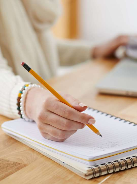 Close-up image of female office worker writing plans in notepad, selective focus